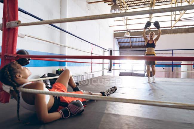 Boxerin feiert, nachdem sie ihre Gegnerin im Boxring im Fitnesscenter niedergeschlagen hat. Starke Kämpferin im Box-Fitness-Training hart. — Stockfoto