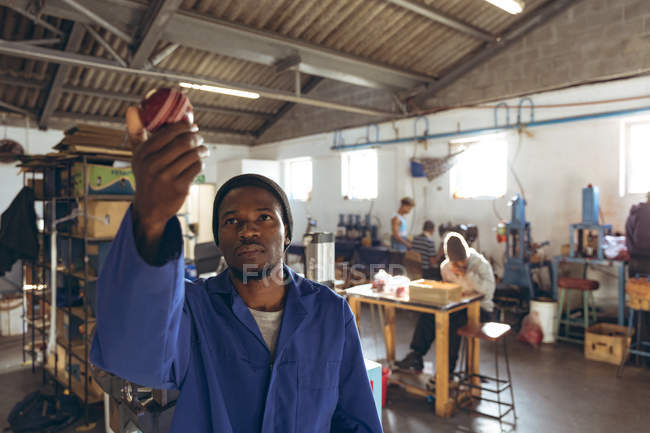 Front view close up of a young African American man holding up a ball to check it in a workshop at a factory making cricket balls, in the background colleagues are working at a workbenches on other parts of the production line. — Stock Photo
