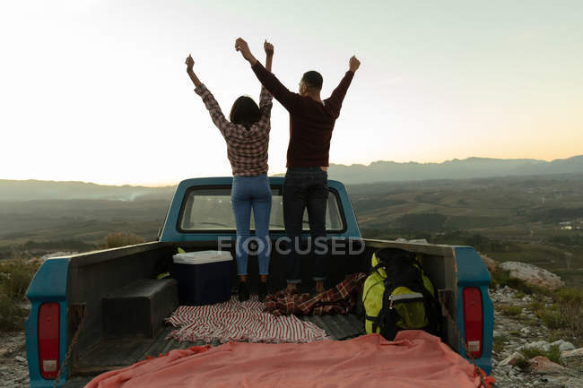 Back view of a young mixed race couple standing on the back of their pick-up truck with their arms raised enjoying the view at sundown during a stop off on a road trip. — Stock Photo