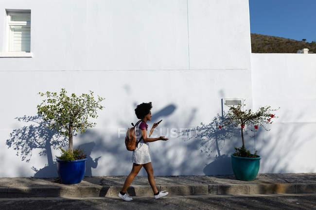 Вид збоку молода жінка змішана гонка проведення рюкзак говорити на смартфон, який вона тримає перед нею, під час прогулянки по міській вулиці на сонці — стокове фото