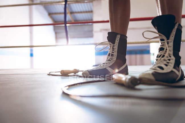 Unterteil einer Boxerin, die im Boxring eines Fitness-Centers steht. Starke Kämpferin im harten Boxtraining. — Stockfoto