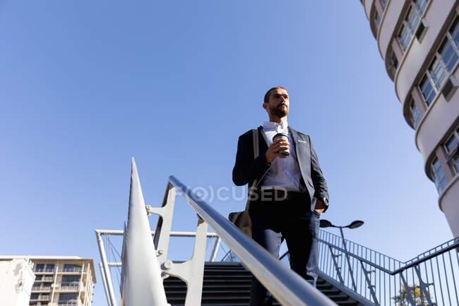 Vista frontale del giovane caucasico che porta una borsa a tracolla e tiene in mano un caffè da asporto scendendo i gradini fuori al sole. Nomade digitale in movimento . — Foto stock
