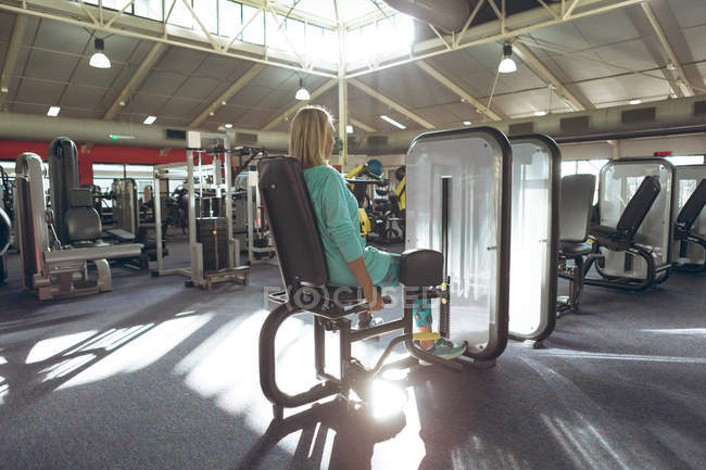 Rear view of disabled active senior woman exercising with leg curl machine in fitness studio — Stock Photo
