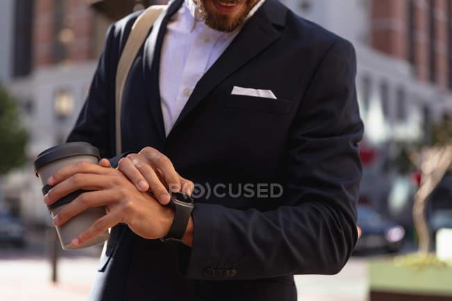 Frontansicht eines jungen kaukasischen Mannes, der auf seiner Uhr die Uhrzeit kontrolliert und einen Kaffee zum Mitnehmen in der Hand hält, der auf einer Straße in der Stadt steht. Digitaler Nomade unterwegs. — Stockfoto