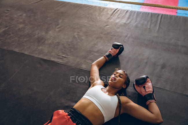 Tired female boxer lying in boxing ring at fitness center. Strong female fighter in boxing gym training hard. — Stock Photo