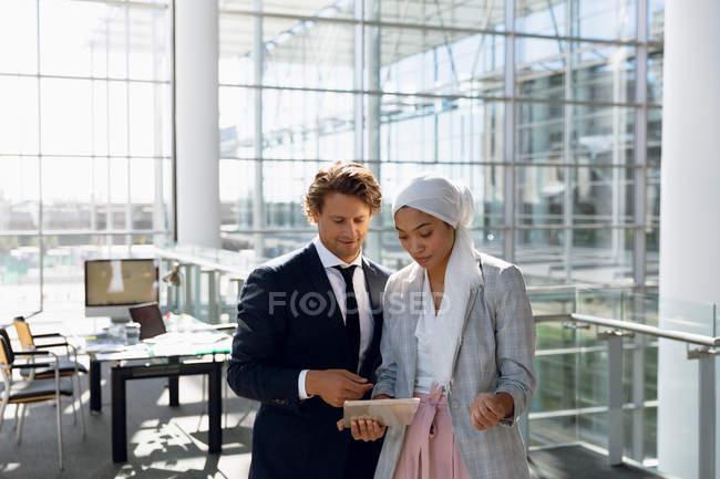 Vue de face de gens d'affaires travaillant ensemble sur tablette numérique dans un bureau moderne . — Photo de stock