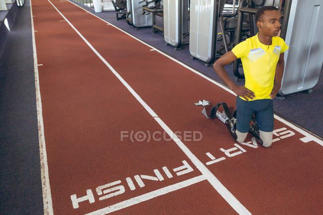 Vue de face de l'athlète masculin afro-américain handicapé au point de départ sur la piste de course dans le centre de remise en forme — Photo de stock