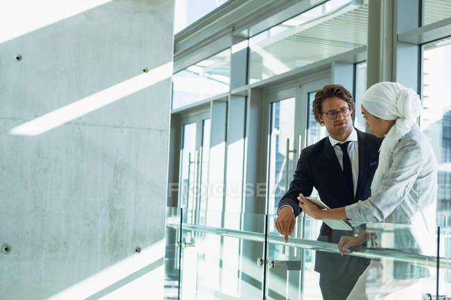 Вид сбоку на бизнес-людей, разговаривающих друг с другом в коридоре в современном офисе . — стоковое фото