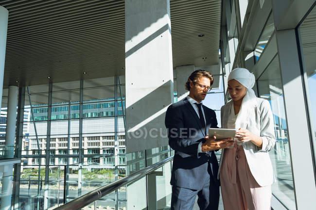 Vista frontale di uomini d'affari che lavorano insieme su tablet digitale in corridoio presso l'ufficio moderno . — Foto stock