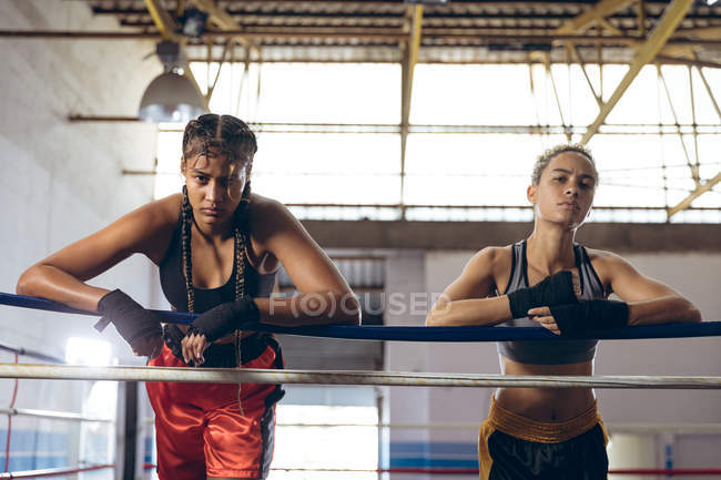 Boxe afro-americano apoiado em cordas e olhando para a câmera no ringue de boxe no clube de boxe. Forte lutador feminino no treinamento de ginásio de boxe duro . — Fotografia de Stock