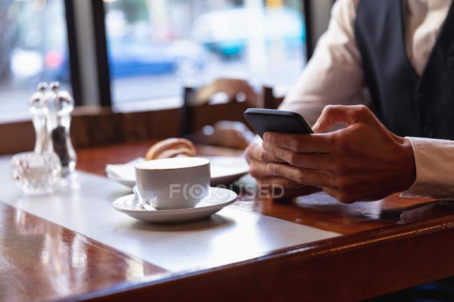 Milieu de la section de l'homme en utilisant smartphone assis à une table à l'intérieur d'un café avec une tasse de café et un croissant. Nomade numérique en mouvement . — Photo de stock