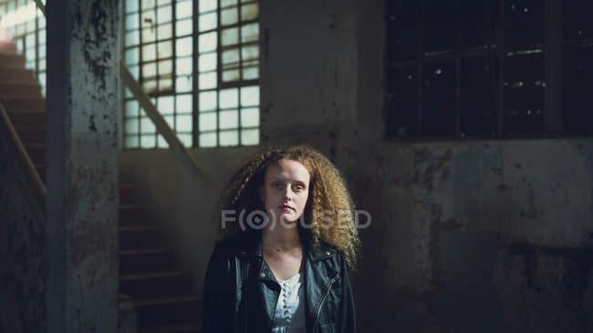 Vista dianteira de uma mulher caucasiano nova com o revestimento de couro desgastando do cabelo curly ao olhar atenta à câmera dentro de um armazém escuro e vazio — Fotografia de Stock