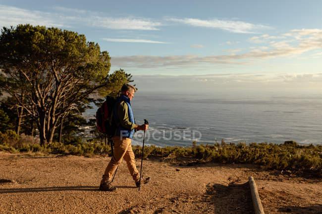 Vue latérale d'un homme caucasien mature portant un sac à dos et utilisant des bâtons de marche nordique marchant vers la côte pendant une randonnée — Photo de stock
