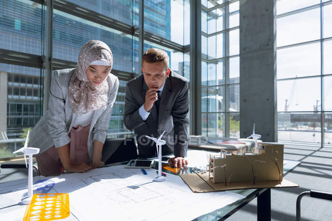 Multi-ethnic male and female architects looking at blueprint in office. — Stock Photo