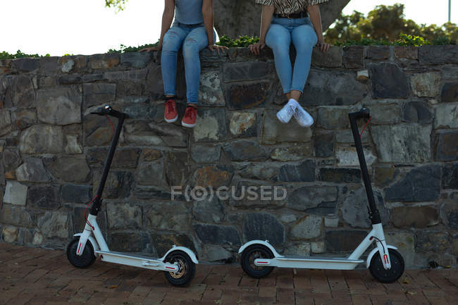 Front view low section of two sisters sitting on a wall in an urban park, with their electric scooters parked below them — Stock Photo
