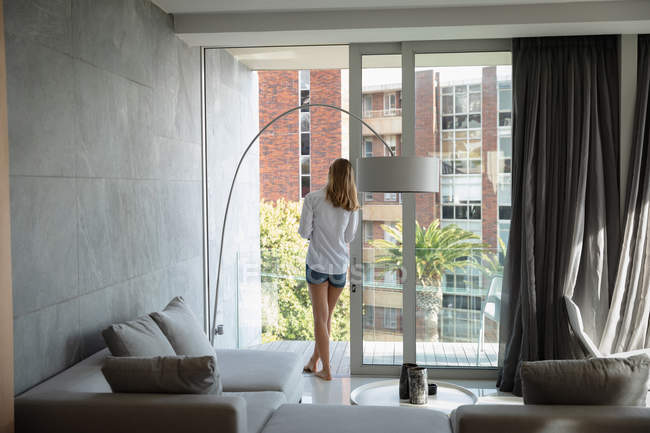 Back view of a young Caucasian woman wearing a white shirt leaning on a balcony door looking out, with buildings in the background. — Stock Photo