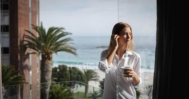 Vista frontale di una giovane donna caucasica con una camicia bianca in piedi su un balcone che regge una tazza di caffè e distoglie lo sguardo, palme e spiaggia sullo sfondo . — Foto stock