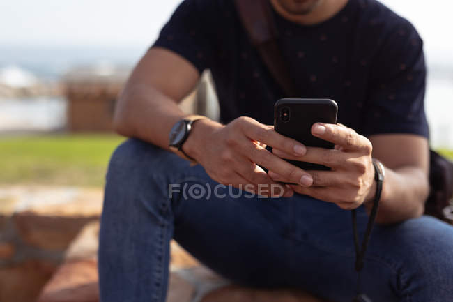 Front view mid section of man sitting outside on a wall using a smartphone in the sun — Stock Photo
