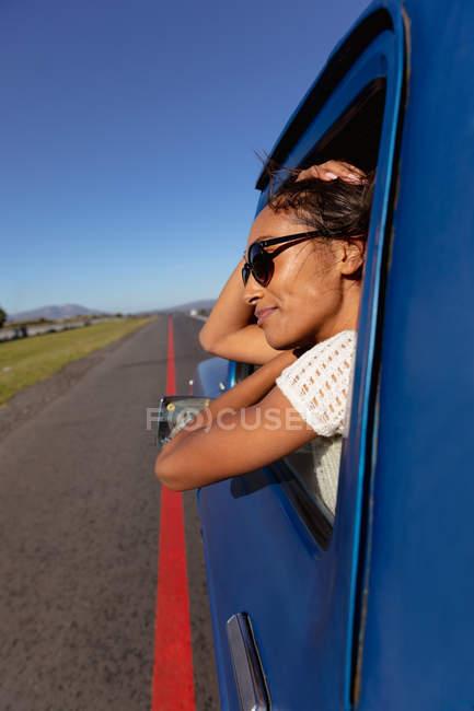 Vue latérale rapprochée d'une jeune femme métisse portant des lunettes de soleil penchée par la fenêtre avant côté passager d'un pick-up souriant, alors qu'elle descend l'autoroute lors d'un road trip — Photo de stock