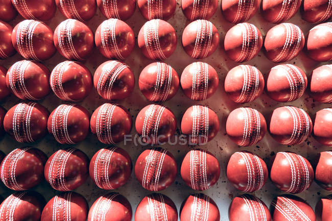Overhead view of red cricket balls in rows at the end of the production line in a factory. — стокове фото
