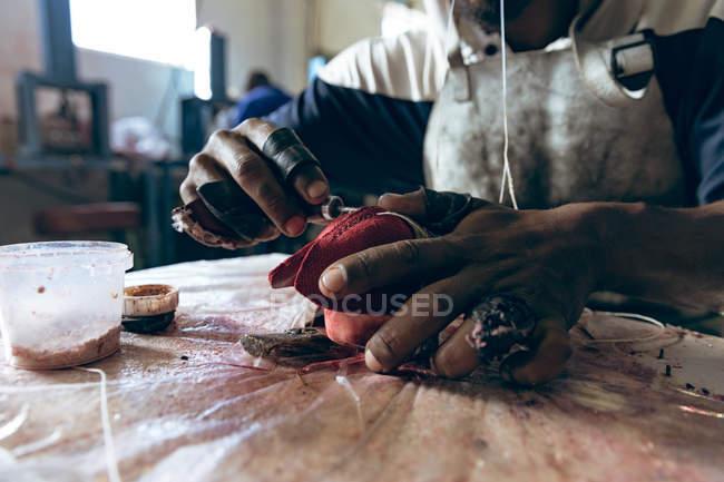 Закрыть руки человека, сидящего на верстаке, сшивающего красные кожаные фигуры на заводе, делающем крикетные шарики . — стоковое фото