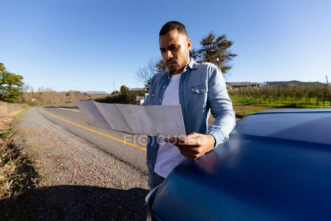 Front view close up of a young mixed race man leaning on the hood of a pick-up truck reading a map during a roadside stop off on a road trip. — Stock Photo