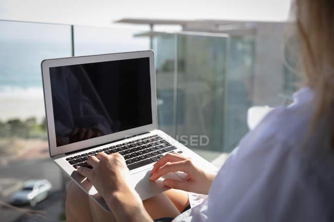 Sobre a vista do ombro de uma mulher vestindo uma camisa branca, sentado em uma varanda usando um laptop, beira-mar e edifícios no fundo . — Fotografia de Stock