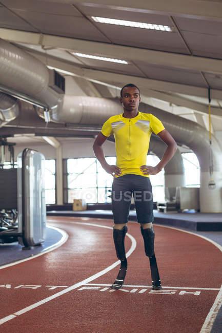 Вид спереди на инвалида афроамериканского спортсмена, стоящего на беговой дорожке в фитнес-центре — стоковое фото
