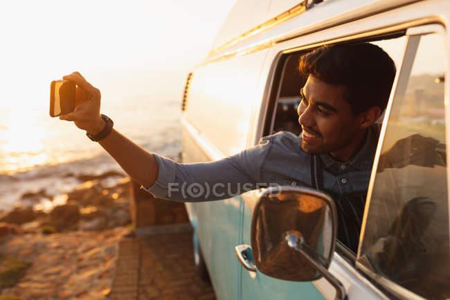 Передний вид молодого смешанного гонщика, сидящего на переднем сиденье фургона, выглядывающего из бокового окна, улыбающегося и делающего селфи со своим смартфоном, освещенного солнечным светом на закате — стоковое фото