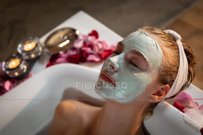 Vista laterale ravvicinata di una giovane donna caucasica sdraiata in un bagno con maschera facciale, con petali e candele accese intorno alla vasca da bagno . — Foto stock