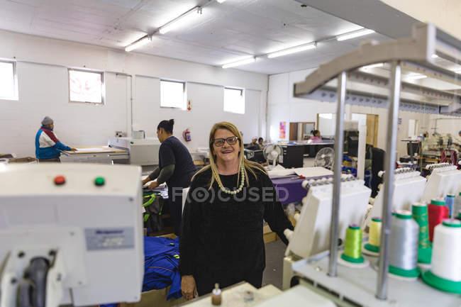Портрет крупним планом середнього віку кавказька жінка стояла поруч з рядами машин в яскраво освітленій спортивного одягу заводу, дивлячись на камеру і посміхаючись. — стокове фото