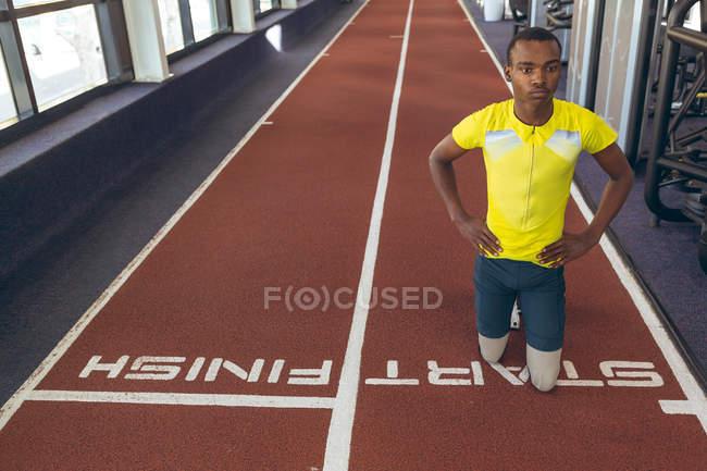 Vista frontal do atlético masculino afro-americano com deficiência no ponto de partida na pista de corrida no centro de fitness — Fotografia de Stock