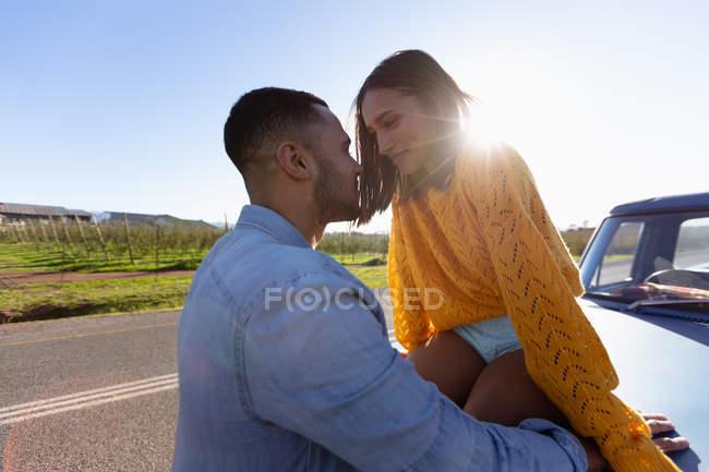 Закройте вид сбоку на молодую пару смешанных рас, наслаждающуюся придорожным перерывом во время дорожного путешествия. Она сидит на капоте их пикапа, они оба улыбаются и собираются поцеловаться. — стоковое фото