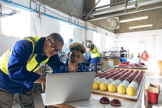 Front view close up of a young mixed race male manager standing and looking at a laptop with a young mixed race male worker sitting at a workbench with finished cricket balls at a cricket ball factory. — Stock Photo