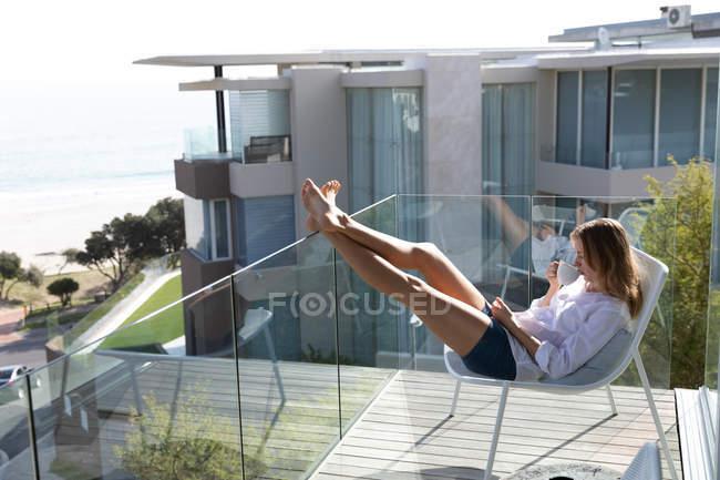 Вид сбоку на молодую кавказскую женщину в белой рубашке, сидящую на стуле на балконе с поднятыми ногами, держа чашку кофе и отводя взгляд, море, пляж и здания на заднем плане . — стоковое фото