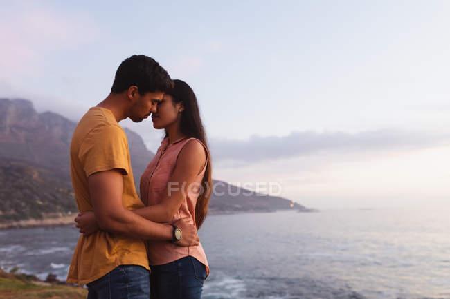 Vue de côté d'un jeune couple mélangé de course restant sur une plage embrassant et s'embrassant au lever du soleil — Photo de stock
