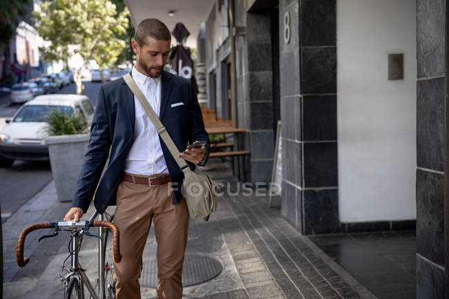 Front view of a young Caucasian man walking, using his smartphone and wheeling his bicycle in a city street. Digital Nomad on the go. — Stock Photo