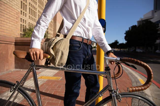 Vista laterale sezione centrale dell'uomo in attesa ad un attraversamento pedonale, mentre cammina con la sua bicicletta in città. Nomade digitale in viaggio. — Foto stock