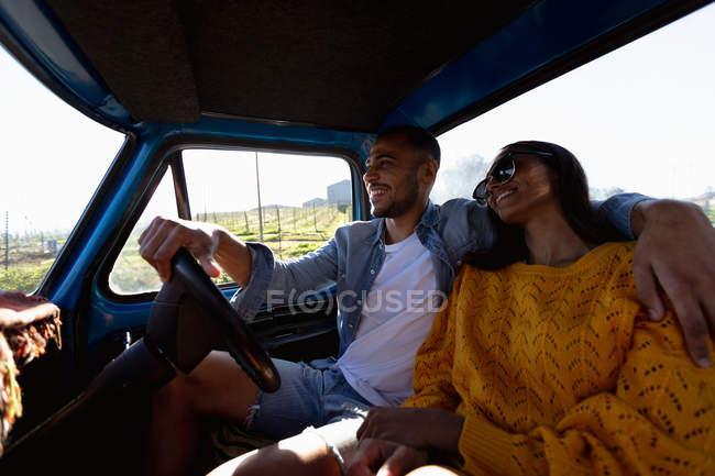 Закройте вид на молодую смешанную расу, сидящую в пикапе, улыбающуюся и обнимающуюся во время дорожного путешествия — стоковое фото