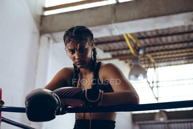 Tiefansicht einer Boxerin mit Boxhandschuhen, die sich an Seile lehnt und im Boxring des Boxclubs in die Kamera blickt. Starke Kämpferin im harten Boxtraining. — Stockfoto