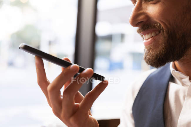 Vista lateral perto da colheita de um jovem caucasiano sorridente fazendo um telefonema segurando seu smartphone na frente de seu rosto, sentado em uma mesa dentro de um café. Digital Nomad em movimento . — Fotografia de Stock