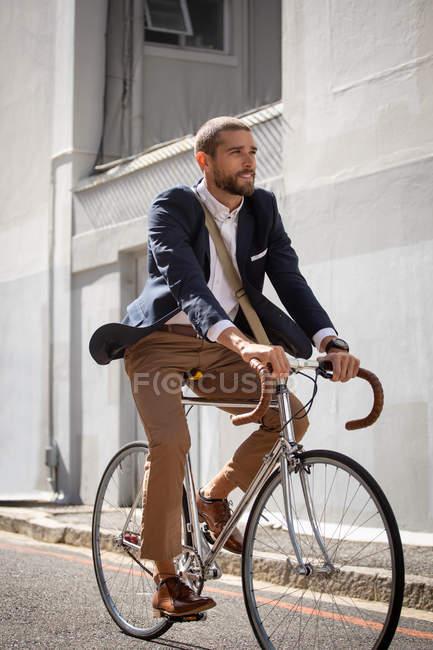 Vista laterale da vicino di un giovane caucasico in bicicletta in una strada della città. Nomade digitale in movimento . — Foto stock