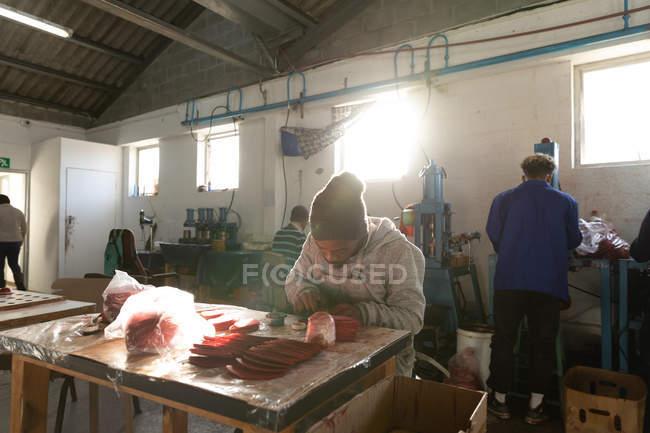 Вид спереди на молодого афроамериканца в шляпе, сидящего на рабочем месте, работающего с вырезанными красными кожаными фигурами в мастерской на заводе по производству крикетных мячей, на заднем плане коллеги работают над другими частями производственной линии . — стоковое фото