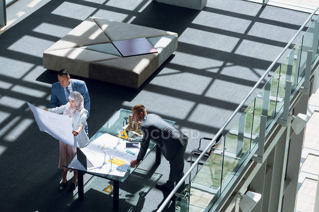 High angle view of male and female architects looking at blueprint in office. — Stock Photo