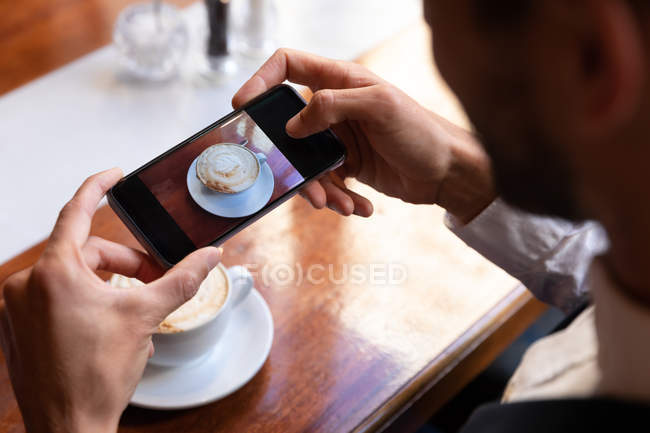 Over the shoulder view of man taking photos of his coffee with a smartphone, sitting at a table inside a cafe. Digital Nomad on the go. — Stock Photo