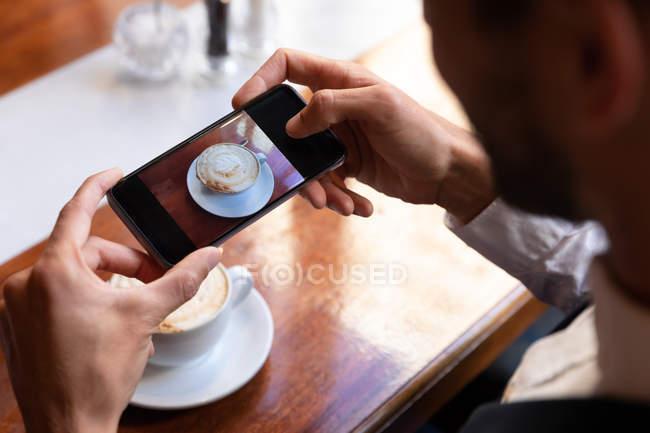 Au-dessus de la vue d'épaule de l'homme prenant des photos de son café avec un smartphone, s'asseyant à une table à l'intérieur d'un café. Nomad numérique en déplacement. — Photo de stock