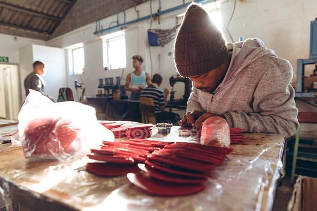 Vista frontal de cerca de un joven afroamericano con un sombrero sentado en un banco de trabajo trabajando con formas de cuero rojo recortadas en un taller en una fábrica de bolas de cricket - foto de stock