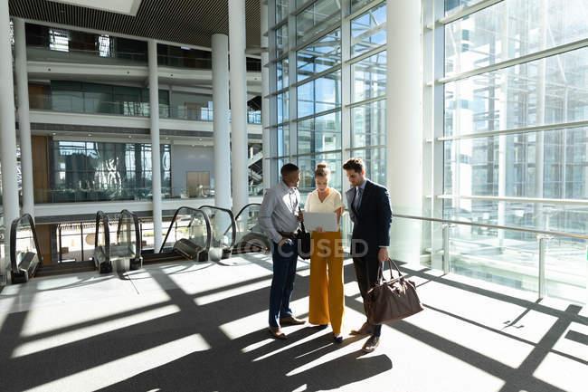 Pleine longueur vue de face de jeune femme d'affaires caucasienne debout entre un jeune afro-américain et un jeune homme d'affaires caucasien regardant un ordinateur portable dans un hall de bureau moderne . — Photo de stock