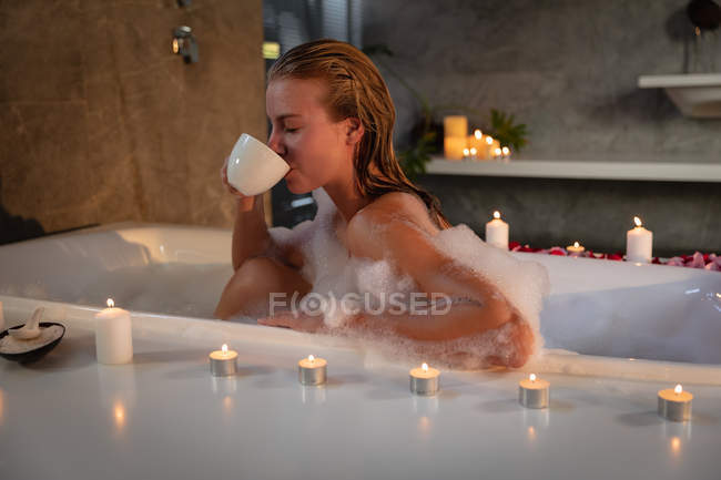 Close up side view of a young Caucasian woman sitting in a foam bath with lit candles around it drinking a cup of tea. — Stock Photo