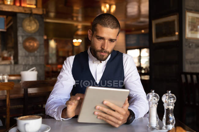 Front view close up of a young Caucasian man using a tablet computer sitting at a table with a coffee inside a cafe. Digital Nomad on the go. — Stock Photo
